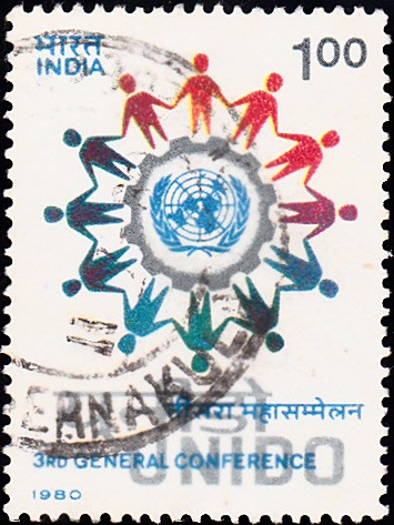 UNIDO : Ring of People encircling U.N. Emblem and Cog-Wheel